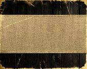 old grunge burlap canvas banner textured with dark wood background