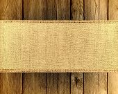 old jute canvas banner textured with dark wood background