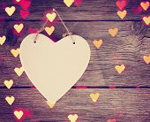 a valentine's day heart on a wooden background with bokeh as an overlay toned with a retro vintage instagram filter effect