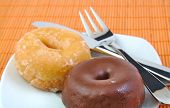 Chocolate and glazed doughnut on wooden background. Donuts.
