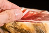 Caucasian man hand takes slices from Serrano ham