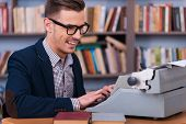 pic of typewriter  - Side view of happy young author typing something at the typewriter and smiling while sitting at his working place with bookshelf in the background - JPG