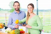 Man and woman unpacking fruits and vegetables out of grocery shopping bag in home kitchen