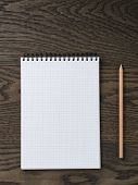 blank notepad with pencil on wood table