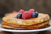Pancakes With Berries And Maple Syrup, On Wooden Table
