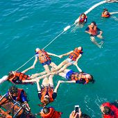 A Group Of Tourists Snorkeling On Blue Sea Water In The Tropical Beach