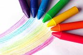 Oil Pastel Crayons Lying On A Paper With Painted Rainbow