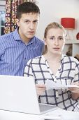 Worried Couple Discussing Domestic Finances At Home