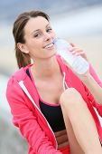 Jogger drinking water from bottle after exercising