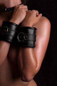 image of sadism  - a beautiful naked body with leather handcuffs - JPG