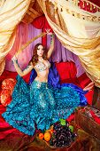 stock photo of harem  - Oriental beauty sitting in a tent and holding a sword - JPG