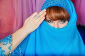 foto of harem  - Young oriental beauty hides her face veil - JPG