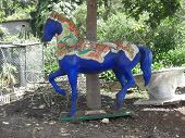image of paint horse  - A brightly painted wooden horse in a public garden in Madeira - JPG