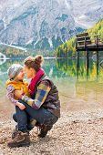 stock photo of eskimos  - A kneeling mother and standing child wearing outdoor gear are giving Eskimo kisses on the shores of Lake Bries - JPG