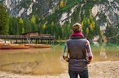 picture of pier a lake  - A brunette woman hiker wearing outdoor gear is standing looking out at the view on Lake Bries - JPG