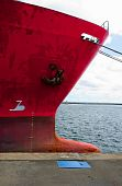 Prow of an old red freighter at wharf