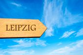 stock photo of leipzig  - Wooden arrow sign pointing destination LEIPZIG GERMANY against clear blue sky with copy space available - JPG