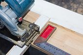 stock photo of degree  - Close up electric circular saw cutting wood and 90 degree iron ruler - JPG