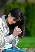 stock photo of biracial  - Young biracial teen girl praying outdoors on bench - JPG
