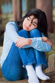 stock photo of biracial  - Sad biracial teen girl in blue shirt and jeans sitting on rocks along lake shore with knees pulled up to chest lonely expression - JPG