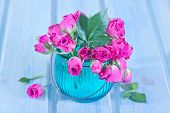 image of bunch roses  - Bunch of small pink Roses in a glass vase over a wooden table - JPG