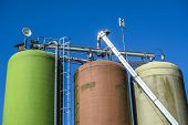 stock photo of silos  - Industrial silos isolated on blue background at a farming industry - JPG