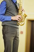 image of saxophone player  - The performer plays a saxophone during a concert - JPG