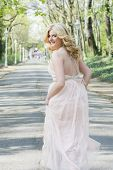 picture of evening gown  - Beautiful blond curly woman wearing evening peach color gown running and looking back - JPG