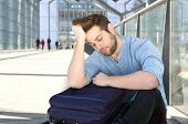 stock photo of sleeping bag  - Portrait of a tired man with bag sleeping at airport