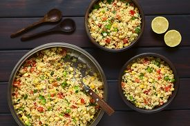stock photo of sweet-corn  - Vegetarian couscous salad made with bell pepper tomato cucumber red onion and sweet corn kernels wooden spoons and lemon on the side - JPG