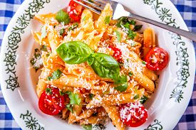 stock photo of pene  - Plate with pasta pene Bolognese sauce cherry tomatoes parsley top and basil leaves on checkered blue tablecloth - JPG