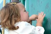 foto of fingerspelling  - little girl imitating sign language gestures printed on a wall at a playground - JPG