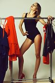 Pretty Girl Posing With Red Dress And Jacket On Hangers poster