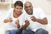 African American couple, man and woman, having fun playing video console games together.