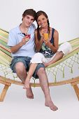 Young couple sitting in a hammock with drinks
