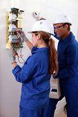 un joven electricista mujer utilizando un amperímetro para comprobar un medidor de electricidad y un reloj de hombre mayor