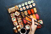 Sushi set. Sushi maki, gunkan and sushi rolls served on stone slate. Japanese food  poster