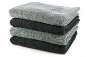 stacked black and grey bathroom towels on a white background
