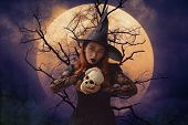 Halloween Witch Holding A Skull Standing Over Dead Tree, Full Moon And Spooky Cloudy Sky, Halloween  poster