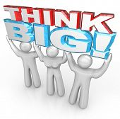 A team of people lift the words Think Big to symbolize achieving great success by setting your sight