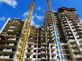 Construction Of Multi-storey Concrete House. Commercial Construction. Two Cranes Near The Building U poster