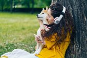 Happy Lady In Headphones Is Listening To Music Using Modern Smartphone And Hugging Shiba Inu Pet Dog poster