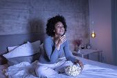 Beautiful Mixed Race Woman Wearing Pajamas Sitting On Bed, Eating Popcorn And Watching A Comedy Movi poster