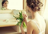 Beautiful bride in white lingerie with bouquet of white tulips sitting in her bedroom near the mirror, rear view