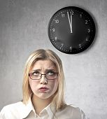 Bored businesswoman looking at a clock