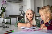 Beautiful senior woman helping little girl with homework. Old grandmother showing granddaughter how  poster