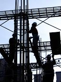 stock photo of scaffolding  - construction workers in outline high up on the scaffolding - JPG