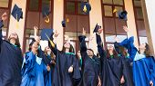 University Graduates  Throwing Graduation Hats In The Air. Group Of Happy Graduates In Academic Dres poster