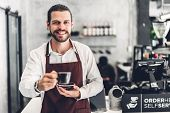 Portrait Of Handsome Bearded Barista Man Small Business Owner Smiling And Holding Cup Of Coffee In T poster