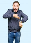 Middle age handsome man wearing a jacket In hurry pointing to watch time, impatience, upset and angr poster